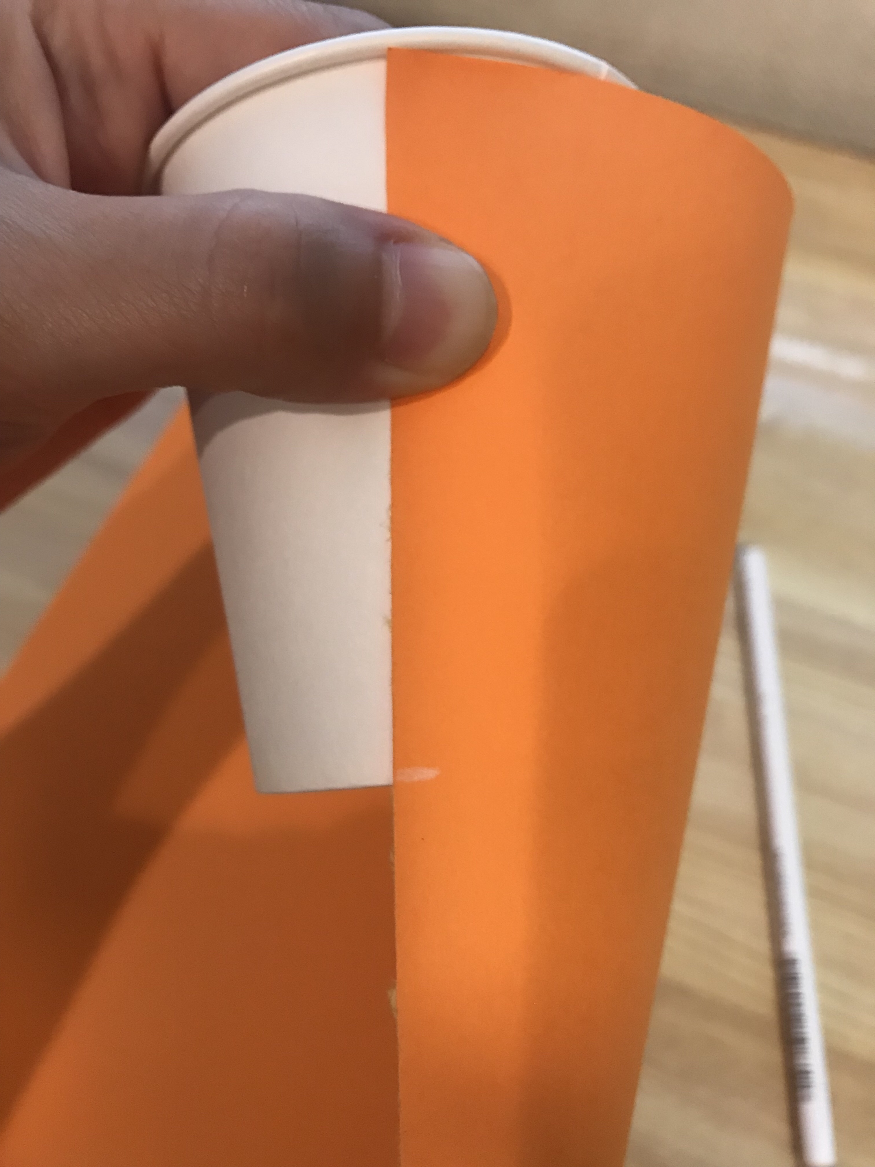 コップに先ほどの画用紙を当てて、コップの高さに印をつけている写真。