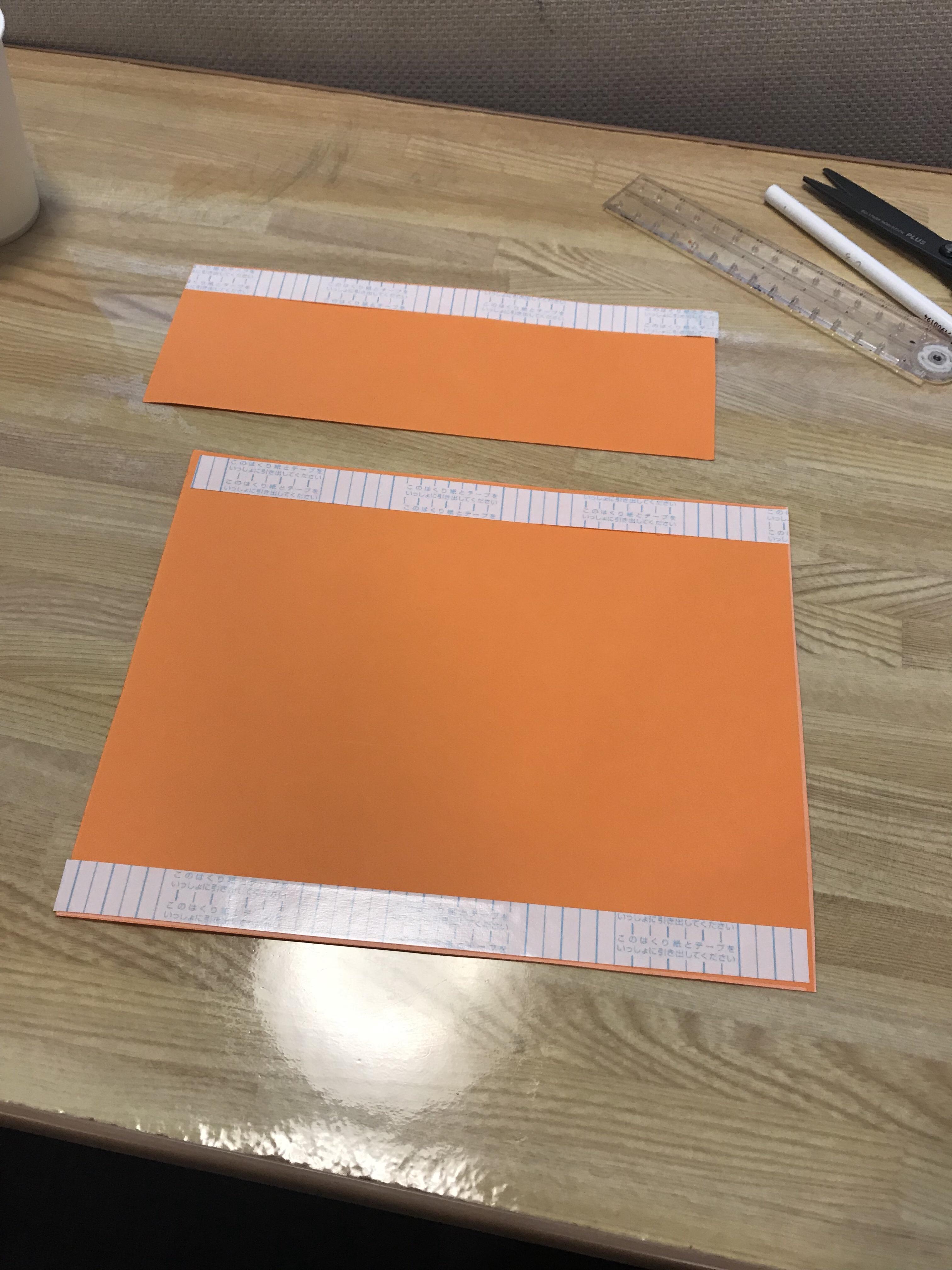 画用紙に両面テープを貼っている写真。