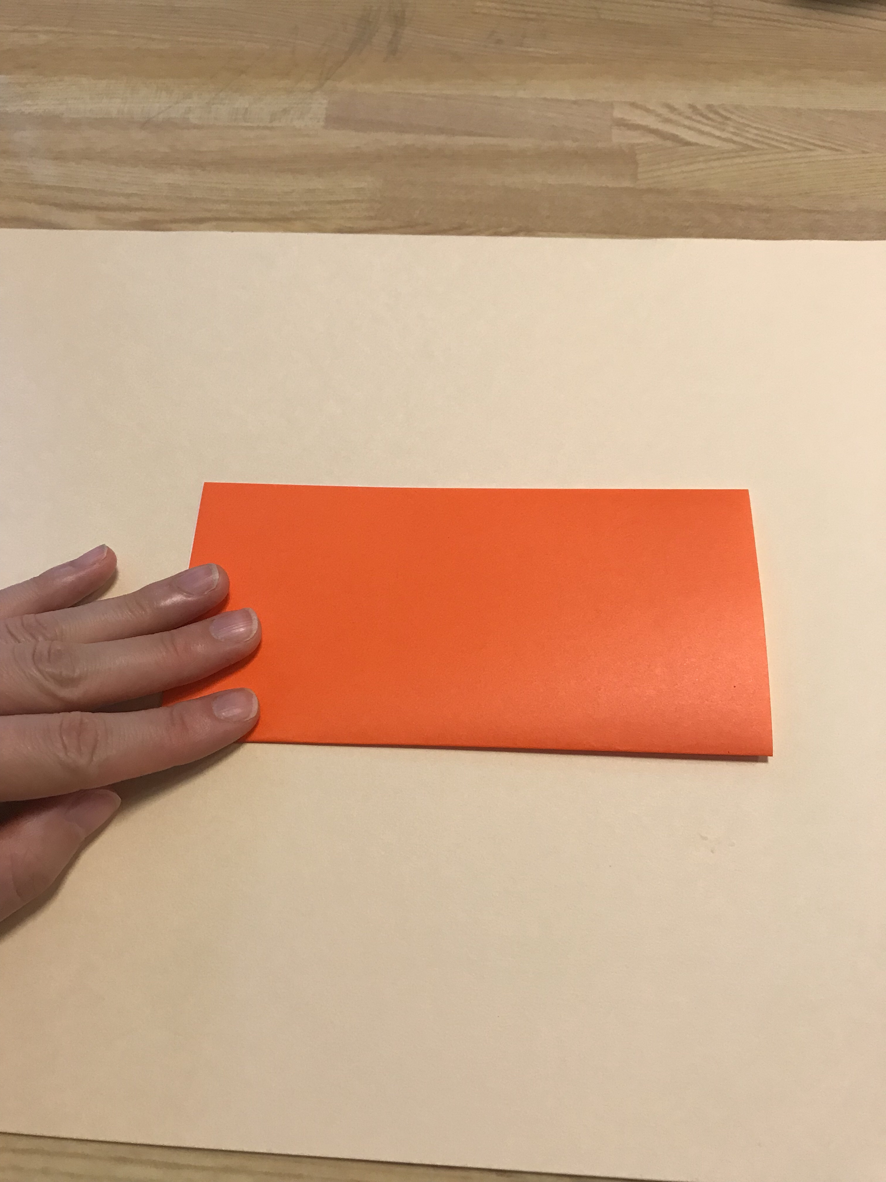 オレンジの折り紙を半分に折っている図