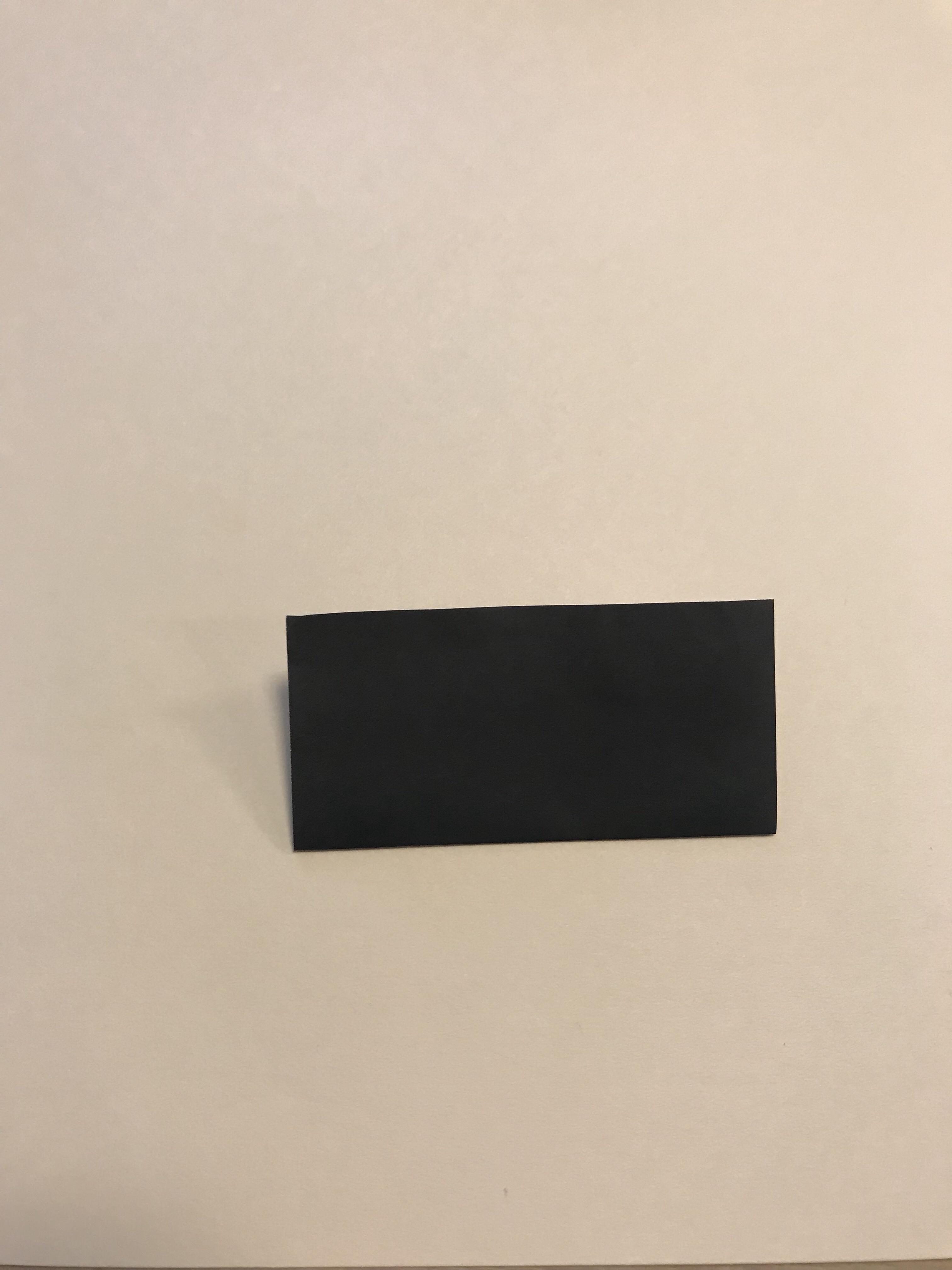 黒い折り紙を半分に折る図。