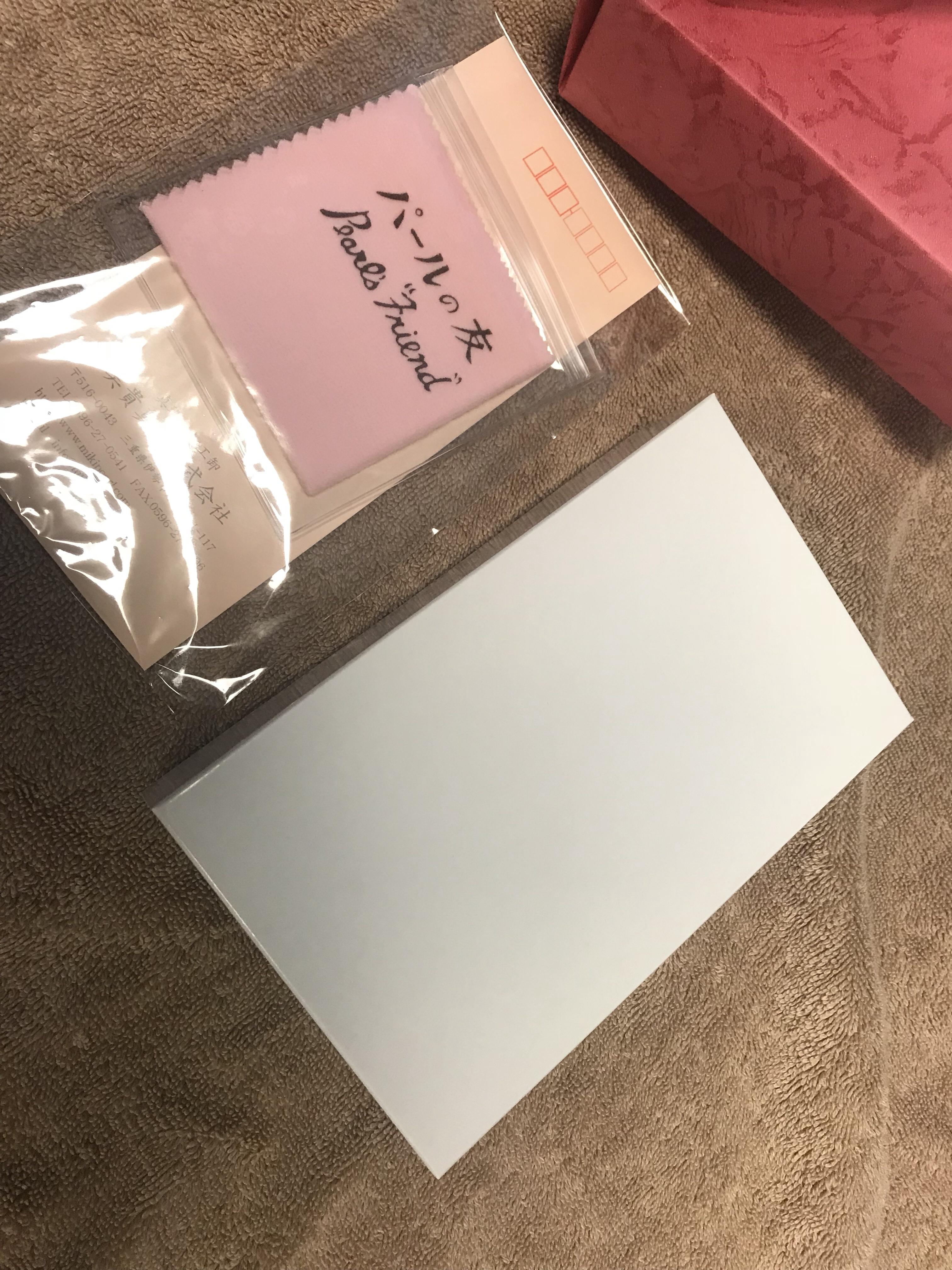 赤い包装を取ると、中に白い箱が。この箱の中に白いジュエリーケースが入っており、その中にネックレスとピアスが収納されています。左に見えるのはパールを磨くクロスです(こちらも無料で付いてきました)。という写真