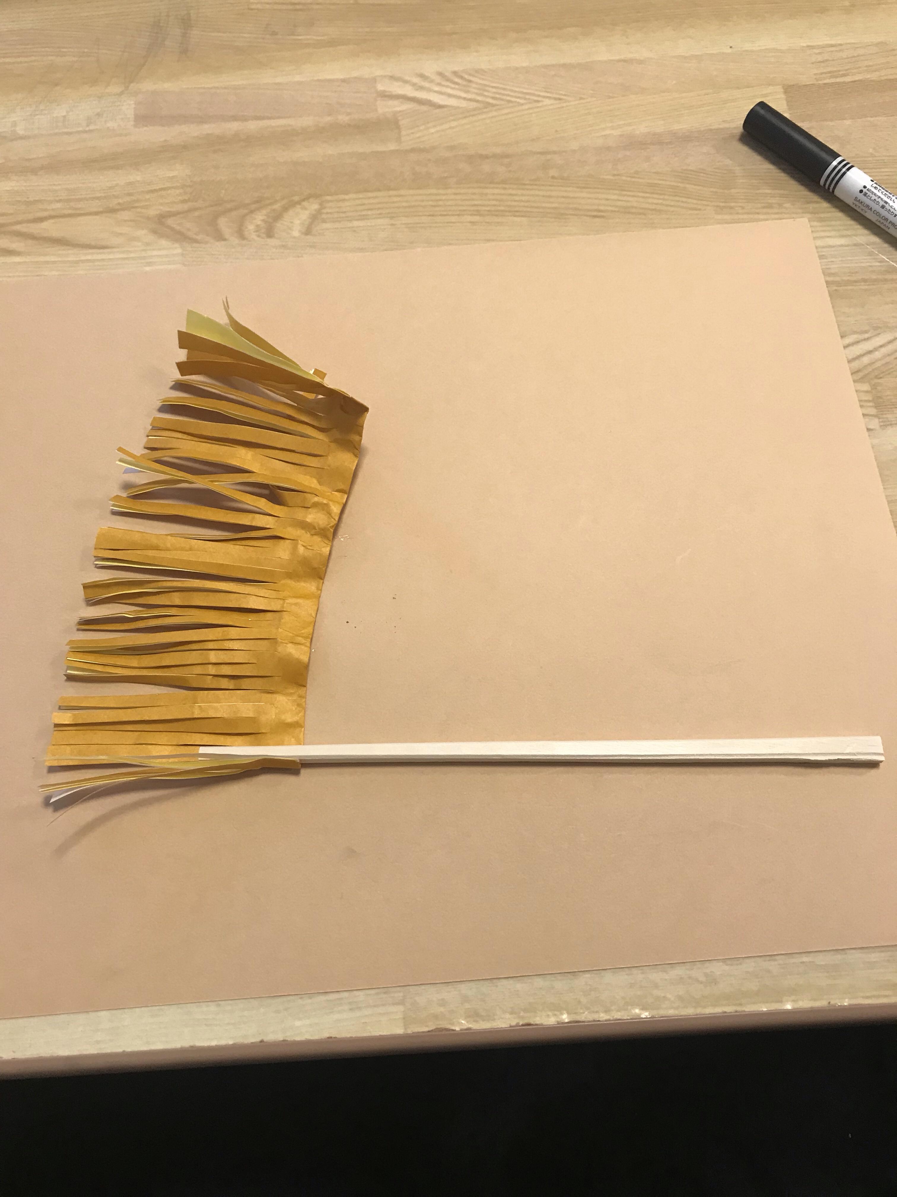 こんな感じで割箸と折り紙を配置して、ぐるぐると巻き付けていきます。という写真